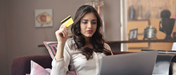 Young woman holding credit card looking at a laptop.